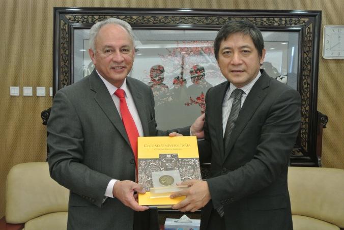 Francisco José Trigo Tavera, secretario de Desarrollo Institucional de la UNAM entrega Peng Long, rector de la Universidad de Estudios Extranjeros de Beijing, un ejemplar conmemorativo de la UNAM.